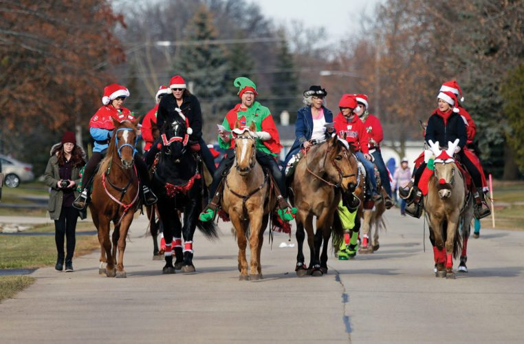 Christmas Caroling by Horseback moves down a street in Fox Crossing, Wis., located near Appleton. Dressed for the occasion, the riders hoped to raise awareness of horses that were rescued from slaughter by A Second Chance Equine Rescue in Larsen, Wis.  Ron Page/The Post-Crescent via AP
