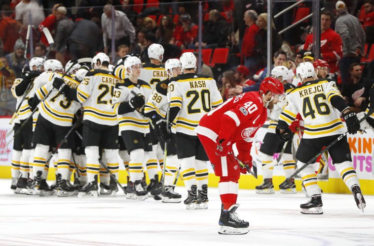 Boston Bruins players celebrate their 3-2 win in overtime as Detroit Red Wings' Henrik Zetterberg (40) skates to the locker room on Wednesday, Dec. 13, 2017, in Detroit. (AP Photo/Paul Sancya)