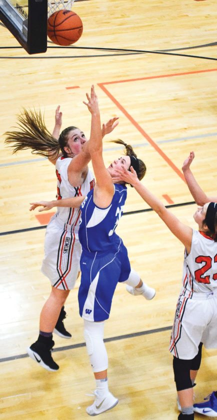 West Iron County's Eden Golliher shoots over Houghton's Kendra Monette on Friday in Houghton. (Bryce Derouin/The Daily Mining Gazette)