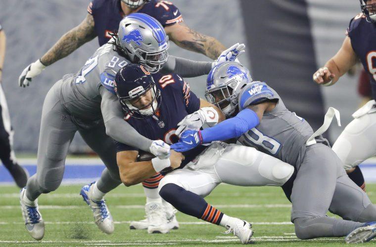Detroit Lions defensive end Ezekiel Ansah (94) and Detroit Lions cornerback Quandre Diggs (28) bring down Chicago Bears quarterback Mitchell Trubisky (10) on Saturday, Dec. 16, 2017 in Detroit. (AP Photo/Paul Sancya)