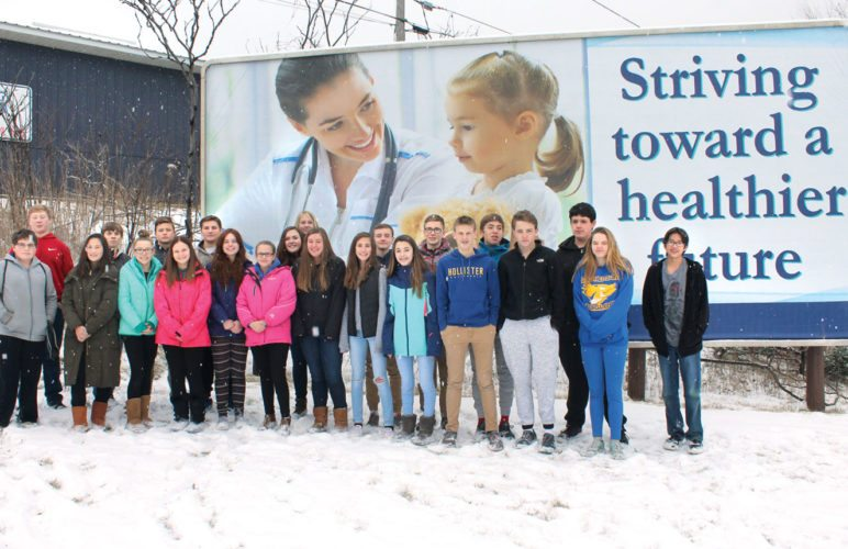 THE KINGSFORD MIDDLE SCHOOL careers class in front of the billboard they helped design for Dickinson County Health Systems. In back, from left, are Anthony Schahczinski, Evan Rittenhouse Witynski, Nolan Pipp, Troy Janosky, Chloe Hull, Dennis Neuens, Trestan Larson, Lucca Rizzo and Daniel Lusk. In front are Zach Milliron, Emma Andrews, Olympia Moore, Cara Aud, Amelia Ellison, Abby Nichols, Alexis Roe, Grace Roberts, Danika Varda, Maegan Dooley, Nathan Bousley, Daniel Weber, Johnnie Pougalski and Isaac Peterson. Not pictured is Kylie Plemel.  (Theresa Proudfit/Daily News photo)