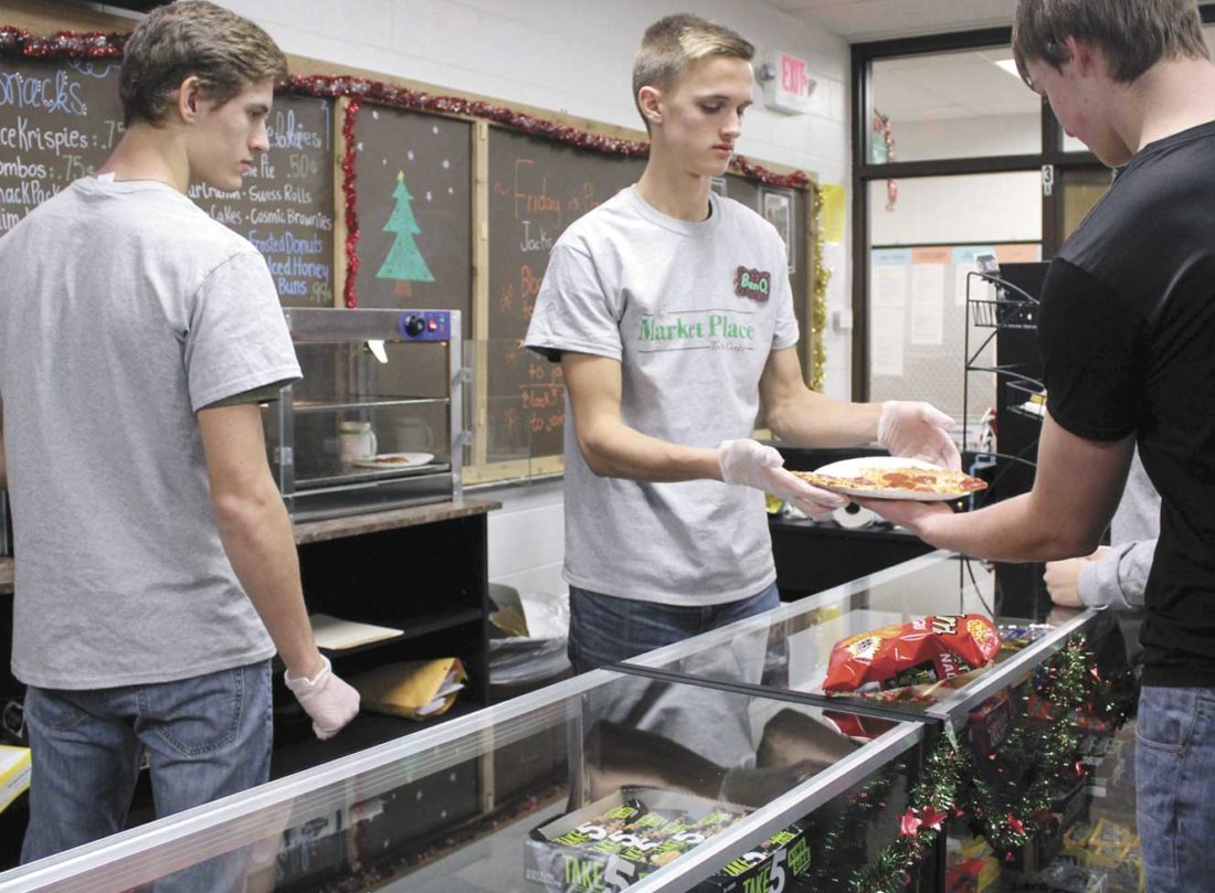 FROM LEFT, JACOB TUCKER and Benjamin Oratch serve pizza to Matthew Bruette at The Market Place, the revamped marketing store at the Dickinson-Iron Intermediate School District Vocational Center. (Theresa Proudfit/Daily News photo)
