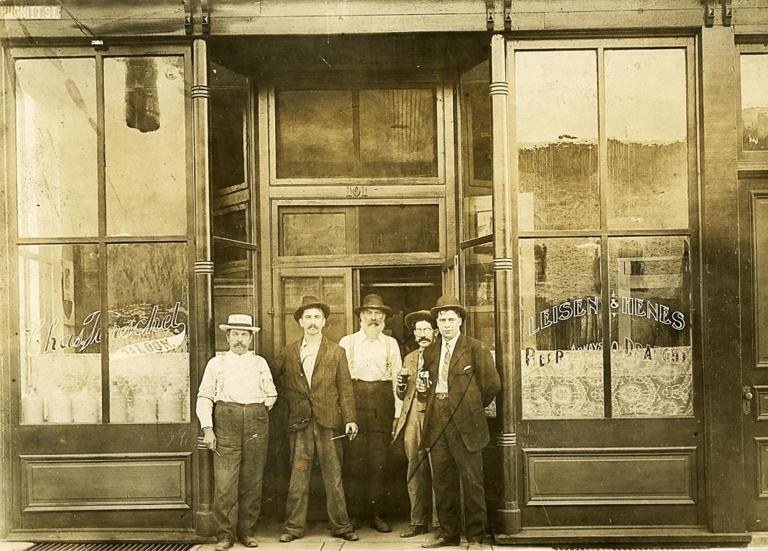 "Charles Tirschel operated a saloon at 101 West Hughitt St., west of the Chicago, Milwaukee & St. Paul Railroad tracks, in downtown Iron Mountain by 1902. By 1905, Joseph Tirschel, standing at the far left, was operating a saloon and serving as an agent for Menominee's Leisen & Henes Brewing Company at 101-103 W. Hughitt St.  Note that ""Leisen & Henes Beer Always on Draught"" was painted on the window at the right. (Menominee Range Historical Museum)"