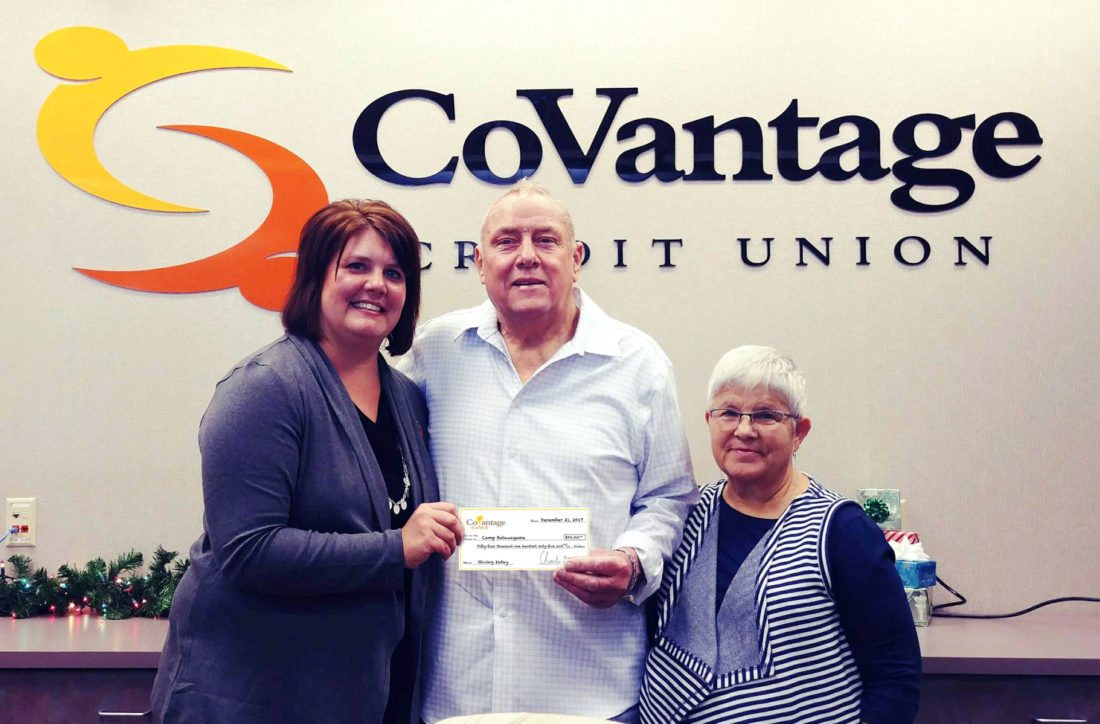 KATIE CLARK, COVANTAGE Credit Union's Crystal Falls branch manager, left, gives a $54,165 check from the CoVantage Cares Foundation Giving Tuesday campaign to Brian and Paula Schulze from Friends of Camp Batawagama in Crystal Falls.