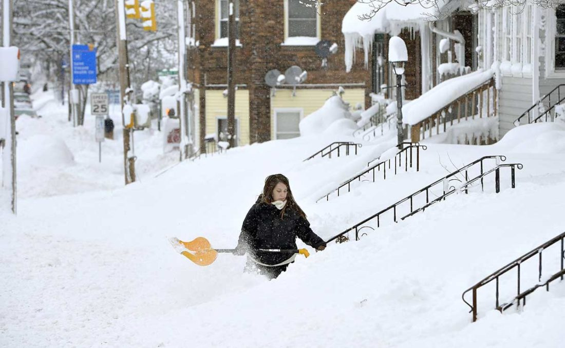 ROCHELLE CARLOTTI SHOVELS near her home in Erie, Pa. The National Weather Service said Monday's storm brought 34 inches of snow, an all-time daily snowfall record for Erie. (Greg Wohlford/Erie Times-News via AP)