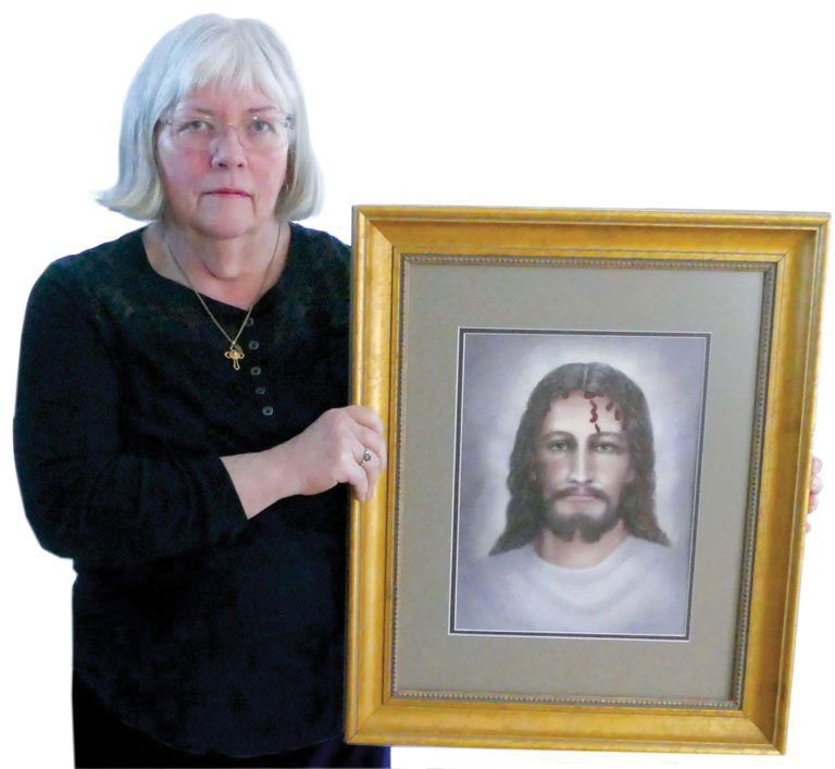 Kathy Falls, a photo restoration specialist of Iron Mountain, holds a retouched image of the face of Christ she created based on the Shroud of Turin. Falls, a photo restoration expert, took the original 1978 image of the shroud by Barrie Schwortz and enhanced it to create her image, which will be recognized next month at the Professional Photographers of America's International Print Competition in Nashville. (Kathy Falls Photo)