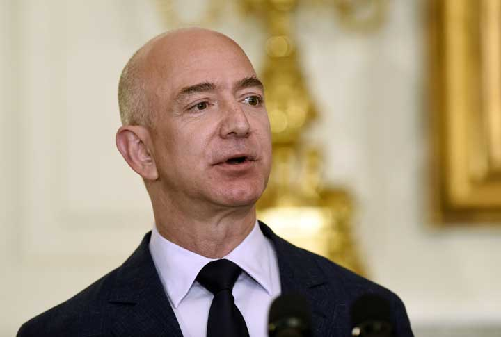 """Jeff Bezos, founder and CEO of Amazon.com, at a May 2016 appearance at the White House. President Donald Trump is criticizing the U.S. Postal Service, asking why it is """"charging Amazon and others so little to deliver their packages."""" (AP Photo/Susan Walsh, File)"""