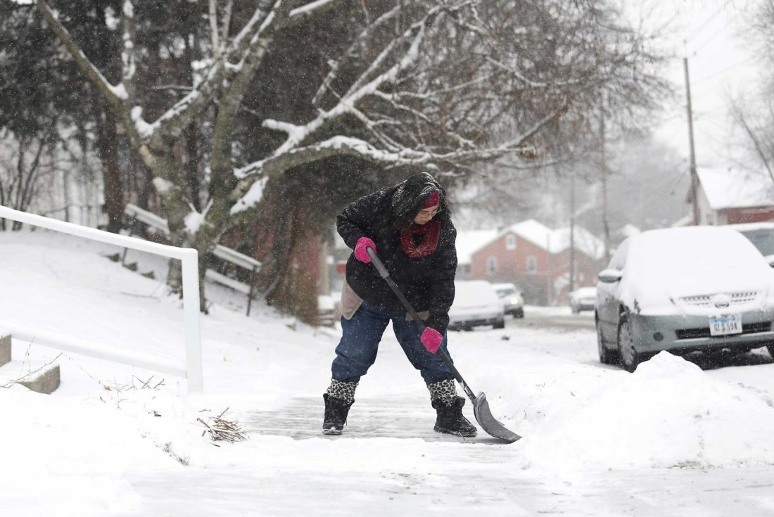 Samantha Dement-Graham shovels her neighbor's sidewalk on University Avenue in Dubuque, Iowa. The National Weather Service is warning of hazardous weather conditions as a deep freeze continues, with temperatures in some locations expected to dip near records not seen in more than 130 years. (Eileen Meslar/Telegraph Herald via AP)