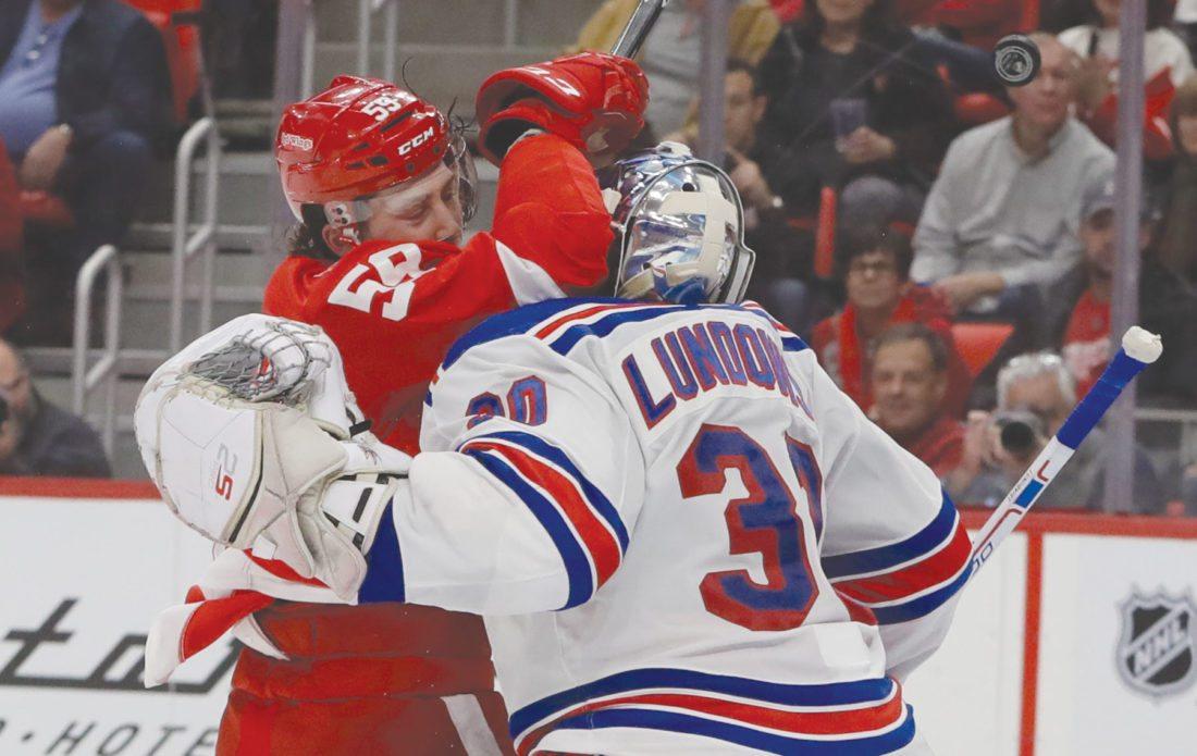 AP Photo Detroit's Tyler Bertuzzi  runs into New York goaltender Henrik Lundqvist (30) to avoid the puck  Friday.