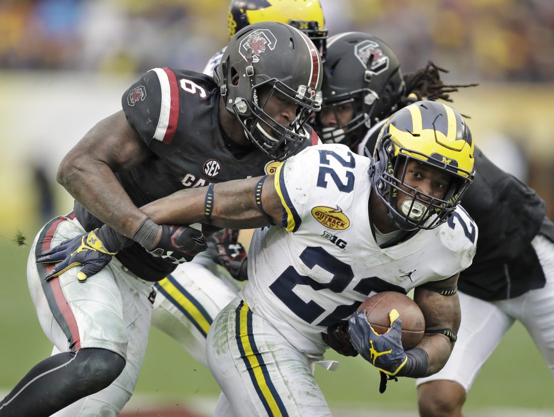 Michigan running back Karan Higdon (22) is stopped by South Carolina linebacker T.J. Brunson (6) during the second half of the Outback Bowl NCAA college football game Monday, Jan. 1, 2018, in Tampa, Fla. South Carolina won the game 26-19. (AP Photo/Chris O'Meara)