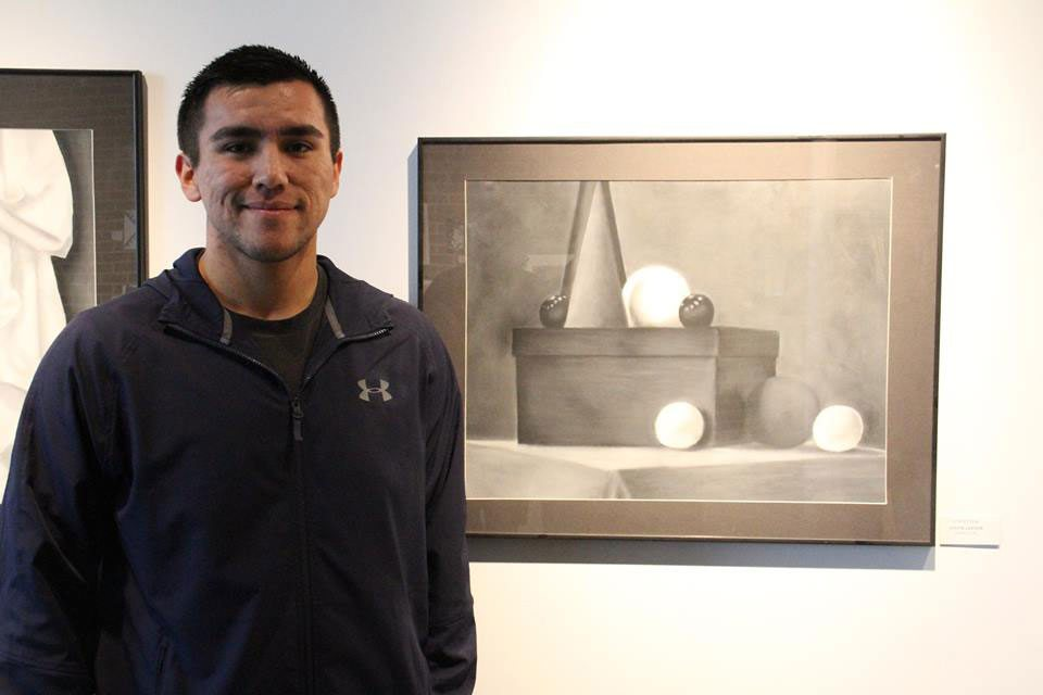 "Bay College student Justin Larson with his charcoal drawing, ""Still Life."""