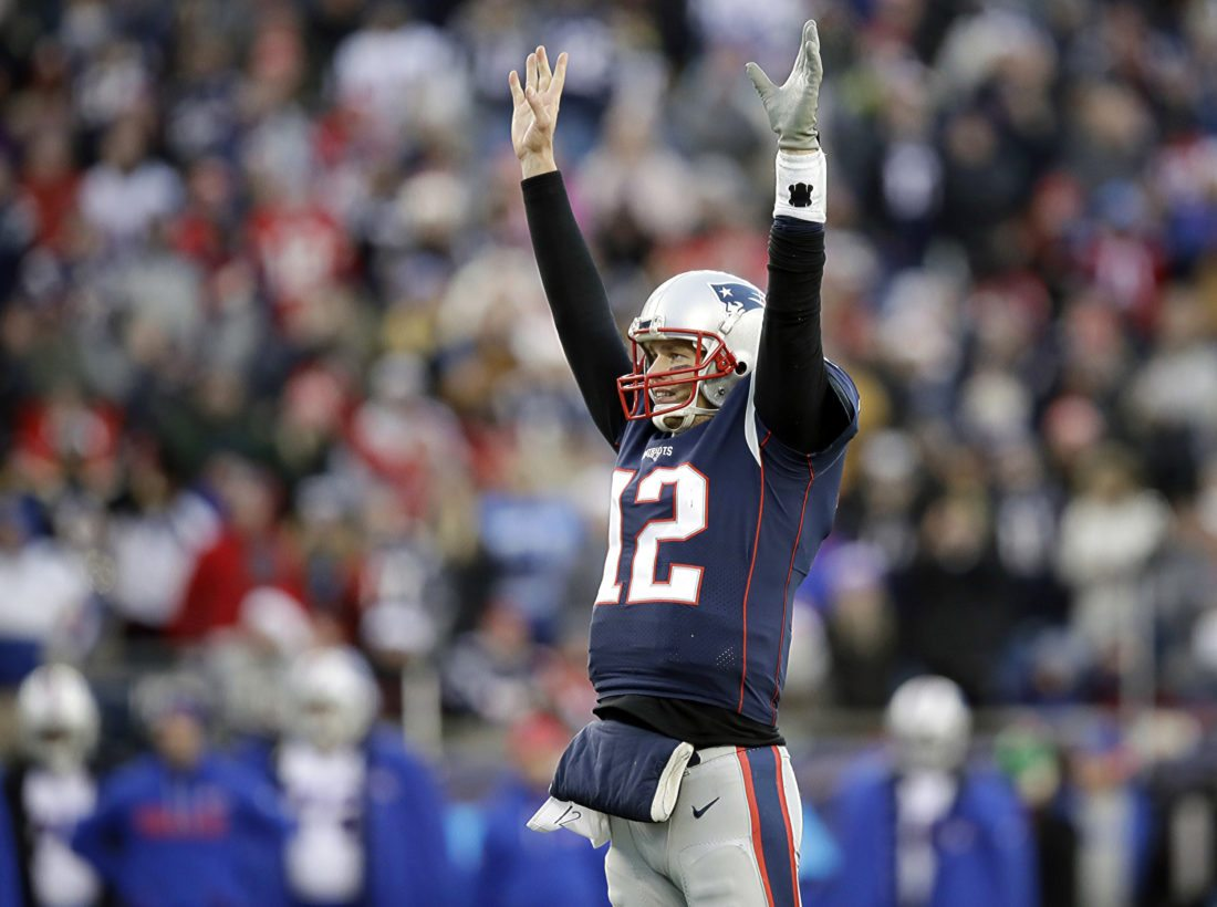 New England Patriots quarterback Tom Brady celebrates a touchdown by running back Dion Lewis on Dec. 24. Brady and the Patriots again top the AFC playoff field.  (AP Photo/Charles Krupa, File)
