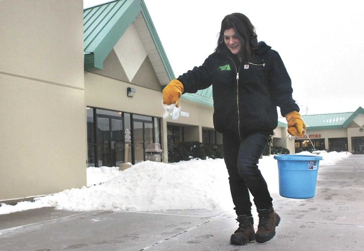 REBECCA PETERSON, PART of the maintenance crew at the Midtown Mall in Iron Mountain, salts the sidewalks outside Super One Foods in Iron Mountain this morning in anticipation of possible freezing rain to come. (Theresa Proudfit/Daily News photo)