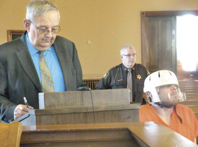 NICKOLAS GOEBEL, RIGHT, awaits sentencing in Iron County Trial Court in a wheelchair and helmet after he appeared to experience seizures at a previous court hearing. At left is defense attorney Geoffrey Lawrence and in the background is Iron County Undersheriff Tom Courchaine. (Nikki Younk/Daily News photo)