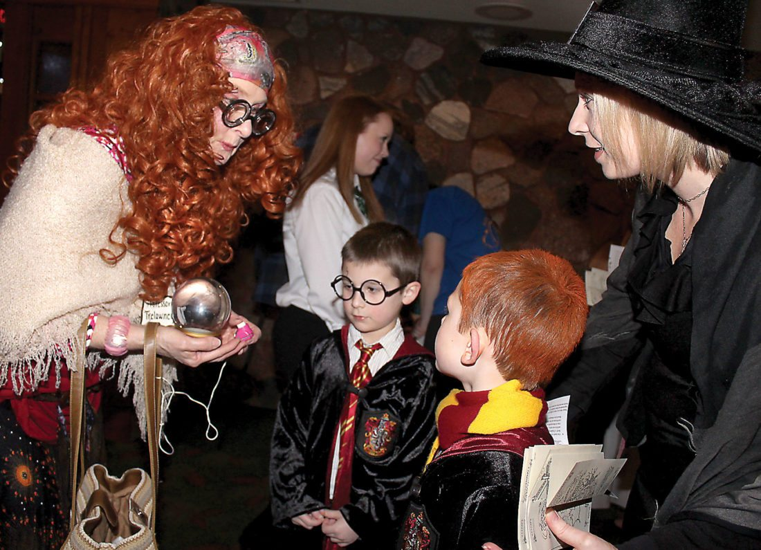 "From left, Professor Sybill Trelawney, aka Barbara Kramer, meets with Levi, Jonah and Dawn Caruso during the ""Christmas in The Wizarding World of Harry Potter"" event Thursday evening at the Pine Grove County Club. (Theresa Proudfit/Daily News photo)"