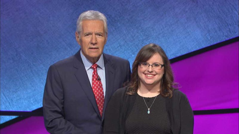 "AMANDA GRIGGS, RIGHT, an Iron Mountain librarian, poses alongside longtime ""Jeopardy!"" game show host Alex Trebek during a taping of the show Oct. 31 in the Los Angeles area. The show in which Griggs, 30, competed will be broadcast locally Wednesday. (Photo courtesy of Jeopardy Productions, Inc.)"
