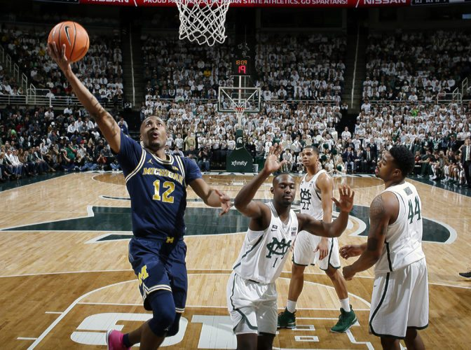 Michigan's Muhammad-Ali Abdur-Rahkman (12) puts up a layup against Michigan State's Joshua Langford (1) and Nick Ward (44) on Saturday in East Lansing. Michigan won 82-72. (AP Photo/Al Goldis)