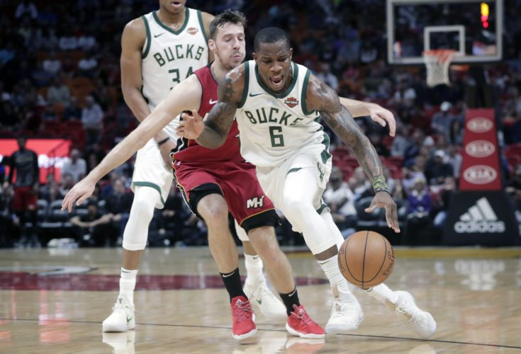 Miami Heat's Goran Dragic, center, defends against Milwaukee Bucks' Eric Bledsoe (6) on Sunday in Miami. (AP Photo/Lynne Sladky)