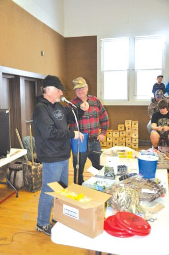 Bob Whitens, left, and Jim Fornetti begin drawing numbers for free prizes at the 2017 Midwinter Trappers Workshop in Hermansville. (Mike Lewis photo)