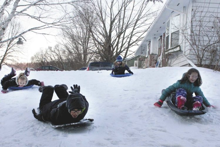 New snow and warmer temperatures in the region spurred a number of area residents to get outside and enjoy some winter activities. From left, Daija Linsmeyer, Carter Hartwell, Aliejae Dubsky and Myla Linsmeyer sled outside their homes on College Street in Quinnesec. (Theresa Proudfit/Daily News photo)