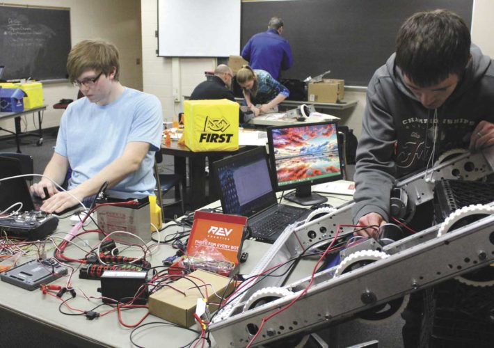 Kingsford students Ben Olson and Blane Newman work on programming and hardwiring one of three robots that will compete in the robotics competition in Escanaba in March. (Theresa Proudfit/Daily News photos)