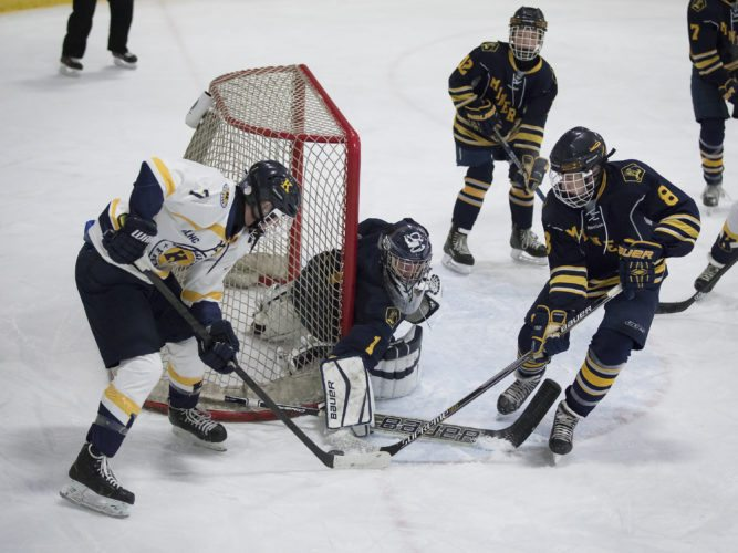 Kingsford's Eli Langston (7) looks for a shot against Negaunee goaltender Nolan Corwin on Tuesday, Feb. 6, 2018, in Iron Mountain, Mich. (Adam Niemi/Iron Mountain Daily News)