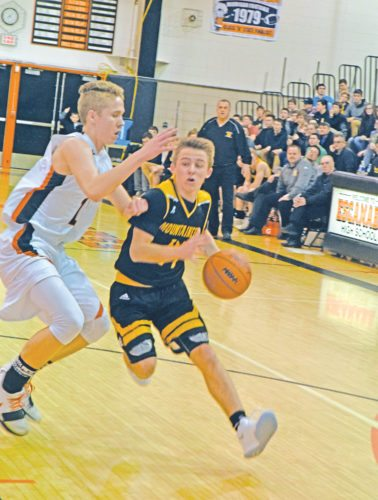 Iron Mountain's Marcus Johnson drives to the basket Tuesday against Escanaba's Peyton Fedell. (Mike Mattson/The Daily Press)