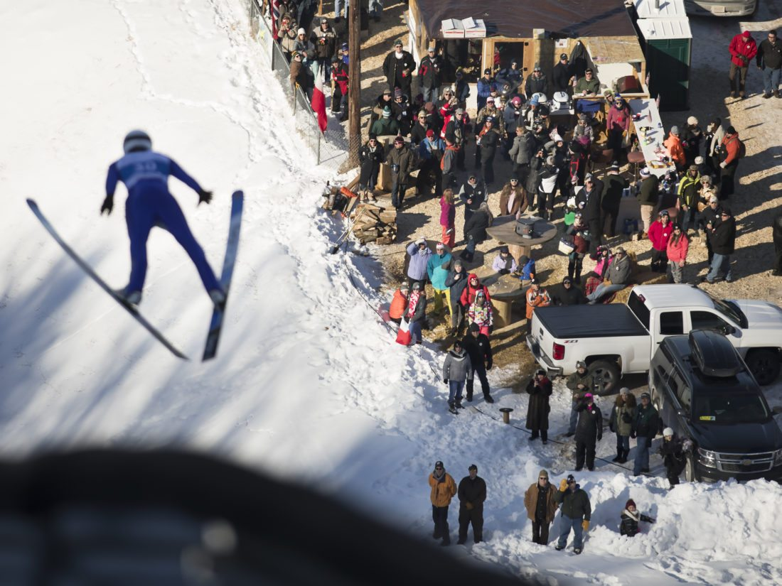 A crowd watches a ski jumper during the Bellin Health Pine Mountain Ski Jumps on Saturday, Feb. 10, 2018, in Iron Mountain, Mich. (Adam Niemi/Iron Mountain Daily News)