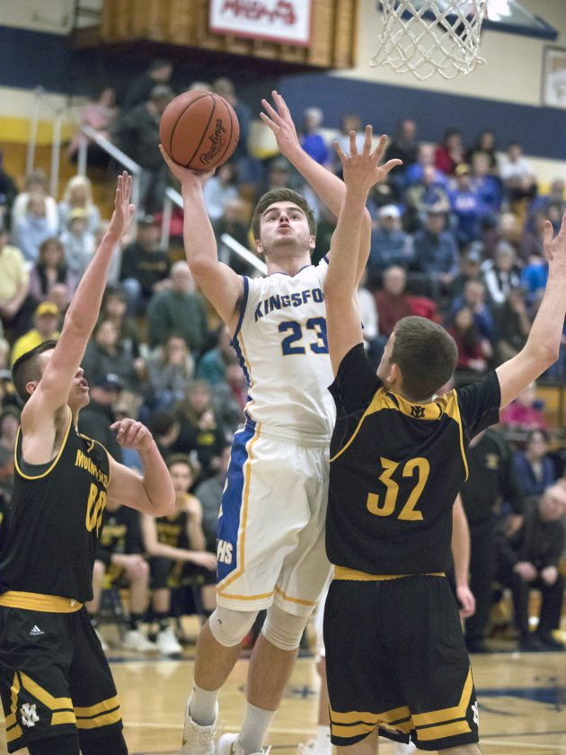Kingsford's Luke Terrian (23) takes a shot over Iron Mountain's Tony Feira (32) and Foster Wonders (00) on Tuesday, Feb. 15, 2018, in Kingsford, Mich. (Adam Niemi/Iron Mountain Daily News)
