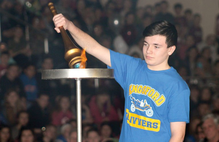 Kingsford student Hunter Skoglund lights the torch during opening ceremonies for the 2018 Great Eight Winter Games, which took place Saturday at Kingsford Middle School. Students from Iron Mountain, Kingsford, Norway, Niagara, Forest Park, West Iron County, Florence and North Dickinson schools competed. (Theresa Proudfit/Daily News photo)