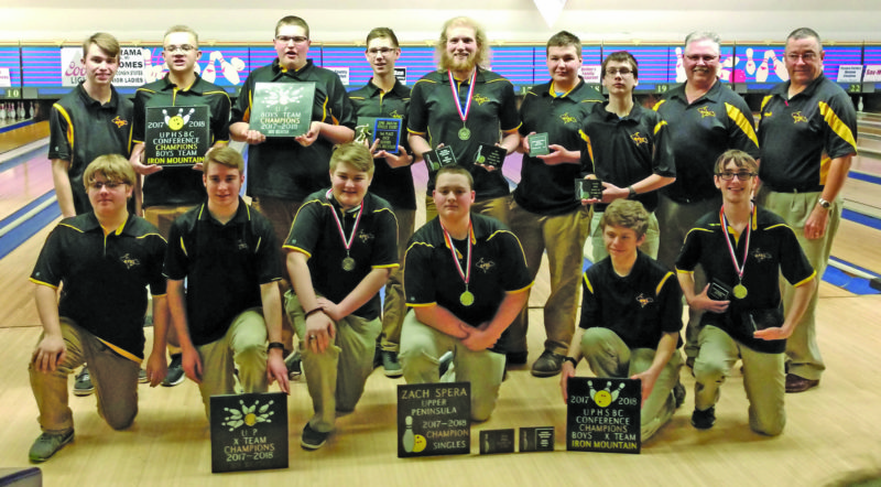 """Avery Bundgaard /The Daily Press Photo Iron Mountain High School boys bowling team poses with its trophies Saturday after winning the UP High School Bowling Conference team finals at the Bowl-A-Rama in Escanaba. The Mountaineers, front, from left: Josh Freeman, Brandon Malburg, Lincoln Pettibone, Zach """"Spanky"""" Spera, Austin Marier and Trey Nichols. Back row: Kurtis Reath, Bryce Robinson, Noah Jacko, Zach Hanson, Ian Driscoll, Brian Pettibone, Nathan Arndt, assistant Kevin Hanson and head coach Pete Tomassoni"""