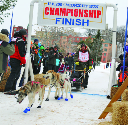 Keith Aili of Ray, Minn. crosses the finish line of the U.P. 200 in first place Sunday morning. (Journal photo by Rachel Oakley)