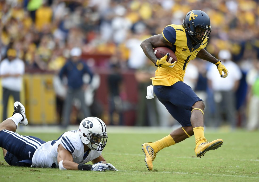 West Virginia wide receiver Shelton Gibson (1) carries the ball past BYU defensive back Eric Takenaka, left, during the first half of an NCAA college football game, Saturday, Sept. 24, 2016, in Landover, Md. (AP Photo/Nick Wass)