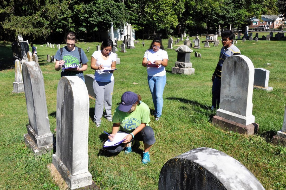 Elizabeth Boyer, kneeling, works with classmates, standing from left, Kayla Eury, Audrey Delos Santos, Joshua Franklin and Bridget Colina to gather the birth and death dates of people buried in Elmwood Cemetery in Shepherdstown for a project in their Shepherd University general ecology class. (Photo courtesy of Shepherd University)