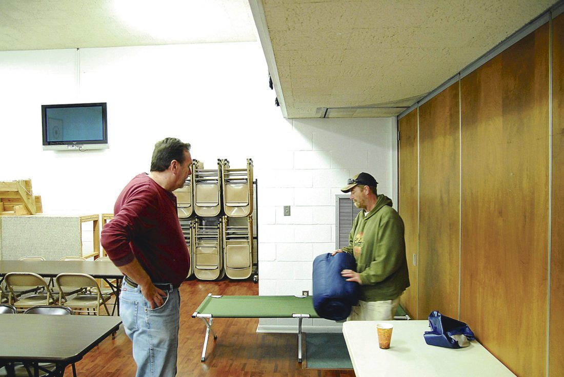 Journal photo by Jeff McCoy Shelter manager John Cloyd, left, helps new resident Jack Hensley get set up on the first night of the cold weather shelter in Jefferson County.