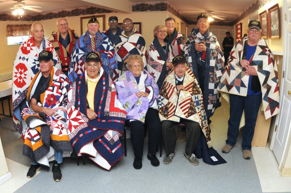 """(Journal photo by Ron Agnir) Local Unsung Heroes are shown with their """"Quilts of Valor"""" on Thursday at The Journal luncheon in Inwood."""