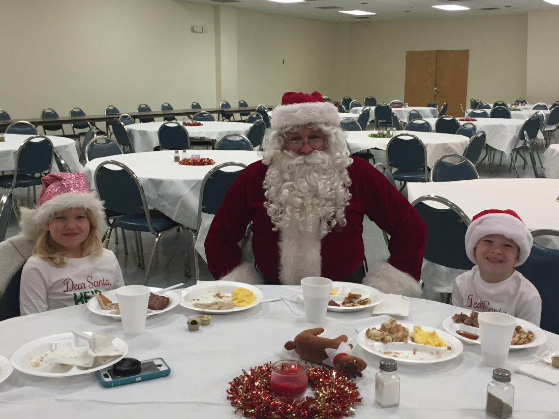 (Shepherdstown Chronicle photo by Toni Milbourne) Santa sits at Independent Fire Company's breakfast with Allie and Camden Burke.