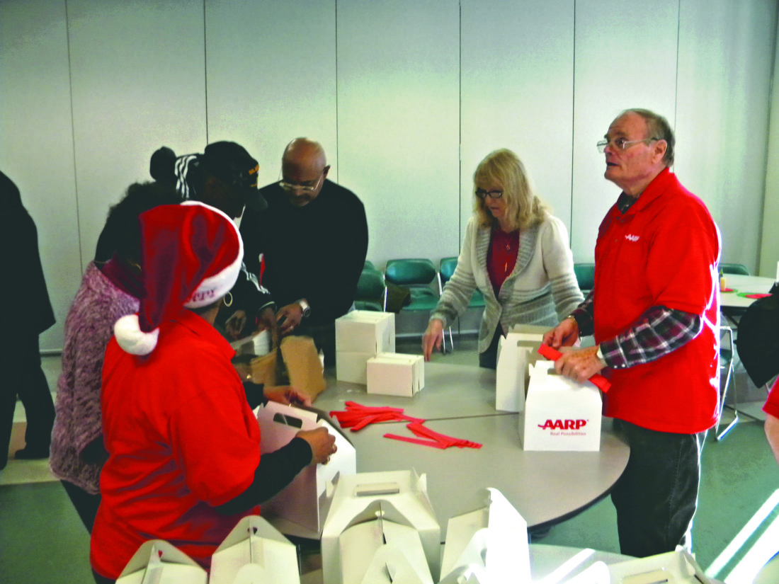 """(Journal photo by Jim McConville) Volunteers with the Martinsburg AARP put together """"blizzard packs"""" for area needy Thursday at the Martinsburg Senior Center."""