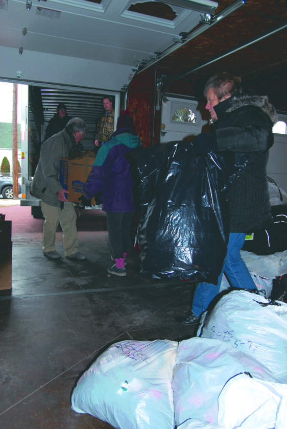Journal photo by Jeff McCoy Volunteers load goods into a truck Friday in Martinsburg that will go to McDowell County for homeless children before Christmas.