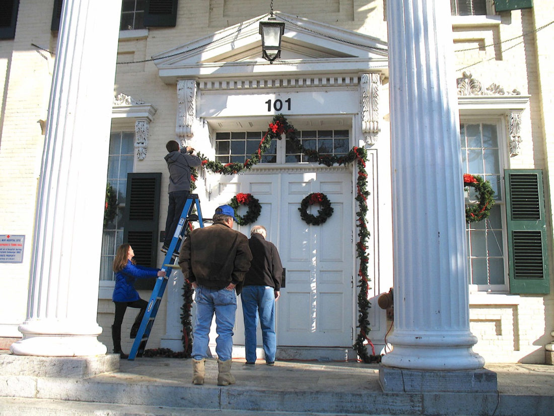 "(Submitted photo) Members of the Shepherdstown Rotary Club and the Shepherd University Rotaract Club gathered in downtown Shepherdstown on Nov. 19 to decorate the town's iconic McMurran Hall building and the town Christmas tree for the upcoming ""Christmas in Shepherdstown"" celebration. The Rotary Club has performed this service for the town each year since these celebrations began nearly 30 years ago. The individuals shown in the photo are, from left to right, Jillian and Garret O'Connell, who are Rotaract Club members, and Jack Lantzy and John Loeffler, of the Rotary Club. This year's ""Christmas in Shepherdstown"" began on Nov. 25 with the mayor's welcome, tree lighting, and Santa's arrival."