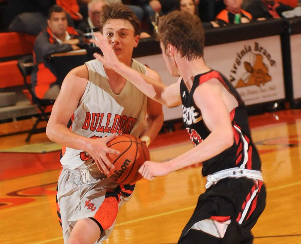 Martinsburg's Steve Edmonds, left, drives to the basket as Heritage's Chris Chapman defends during fourth-quarter action of the Skip Fowler Memorial Tournament championship game Thursday evening in Martinsburg.