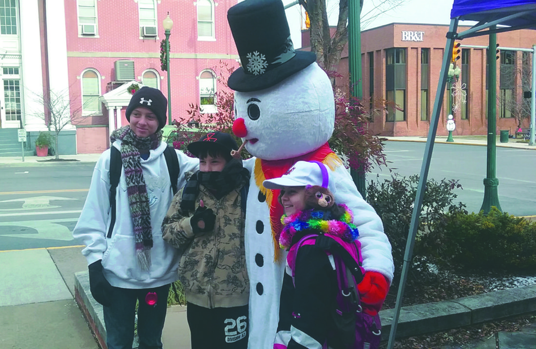 Journal photos by Danyel VanReenen Frosty the Snowman poses with a few participants in the Frosty Family Fun Day on King Street in Martinsburg on Saturday. The event was  hosted by Healthy Berkeley and Main Street Martinsburg.