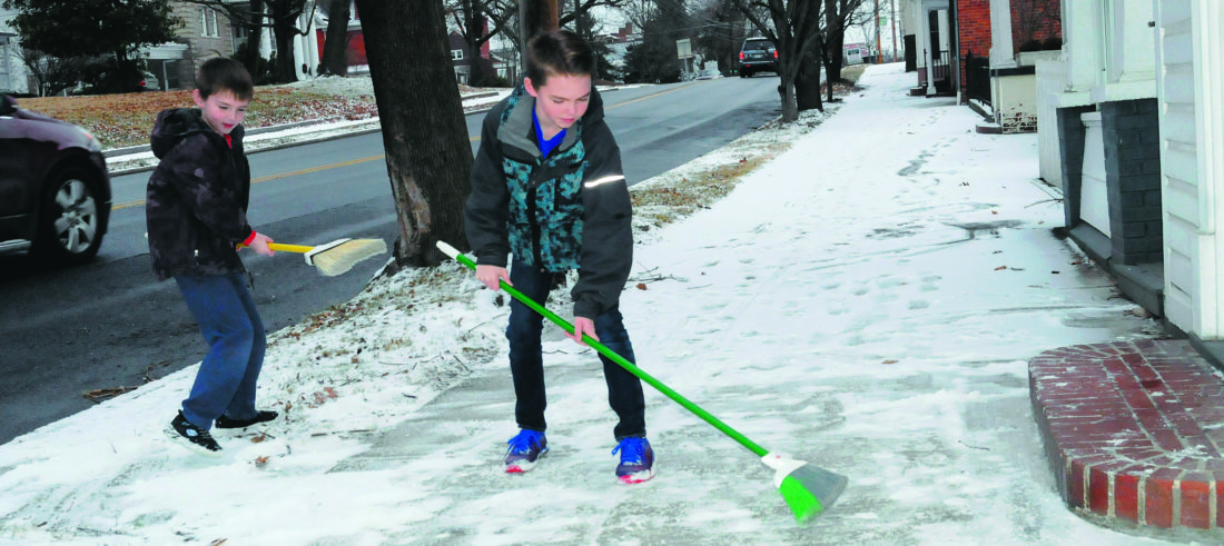 11 Snow Sweepers ra 01-10-17 Brothers Zac Cunningham, 7 yrs old, and Max Cunningham, 9 yrs old, sweep snow off the sidewalk in front of their granma's home  on S. Queen Street Tuesday afternoon after a dusting of snow in the morning. (Journal Photo by Ron Agnir)