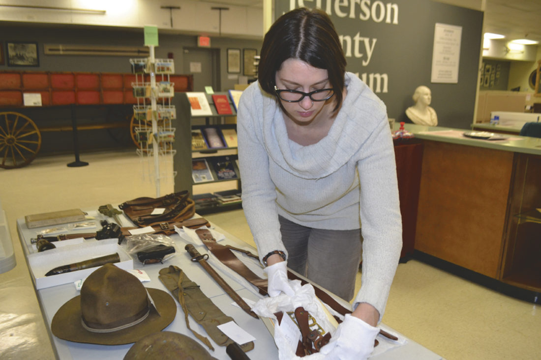 (Journal photo by Mary Stortstrom) Faithe McCreery inspects artifacts from World War I at the Jefferson County Museum.
