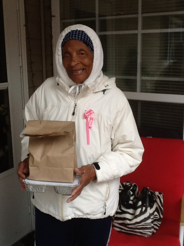(Submitted photo) Connie Knight, recipient of the Berkeley County Meals on Wheels program, smiles as she receives a hot meal delivered to her home.