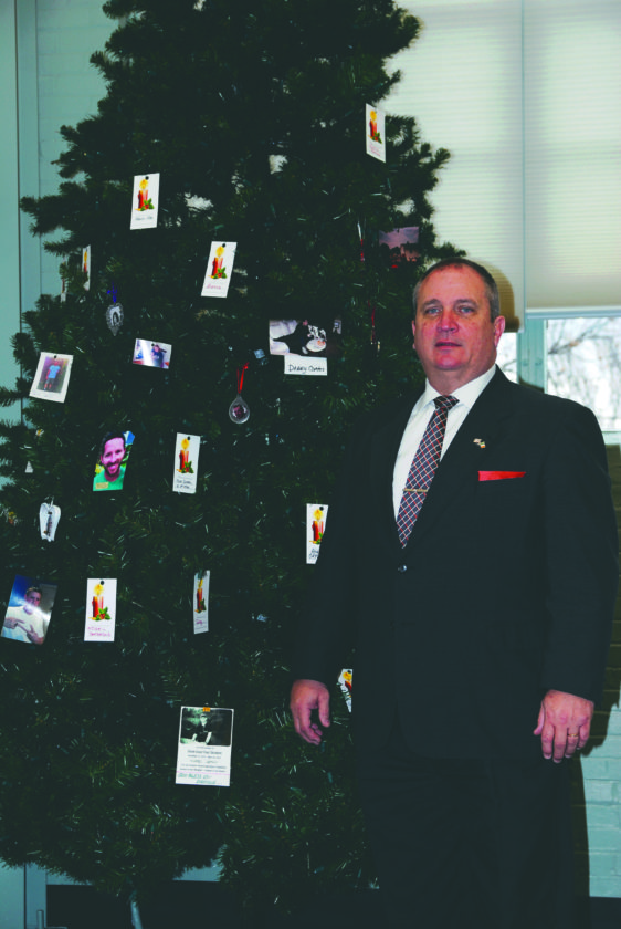 Submitted photo Community Recovery Services Coordinator Kevin Knowles stands in front of the now permanent memorial tree at the Community Recovery Services Office on West Stephen Street in Martinsburg. Loved ones are invited to bring a photo or card to the tree in remembrance of family members or friends who lost their battle with addiction.