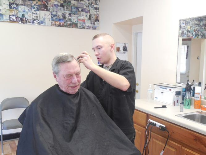 New barber Josh Messner cuts Gail Courtney's hair recently at Weber's Barber Shop in Berkeley Springs. (Photo by Tricia Lynn Strader)