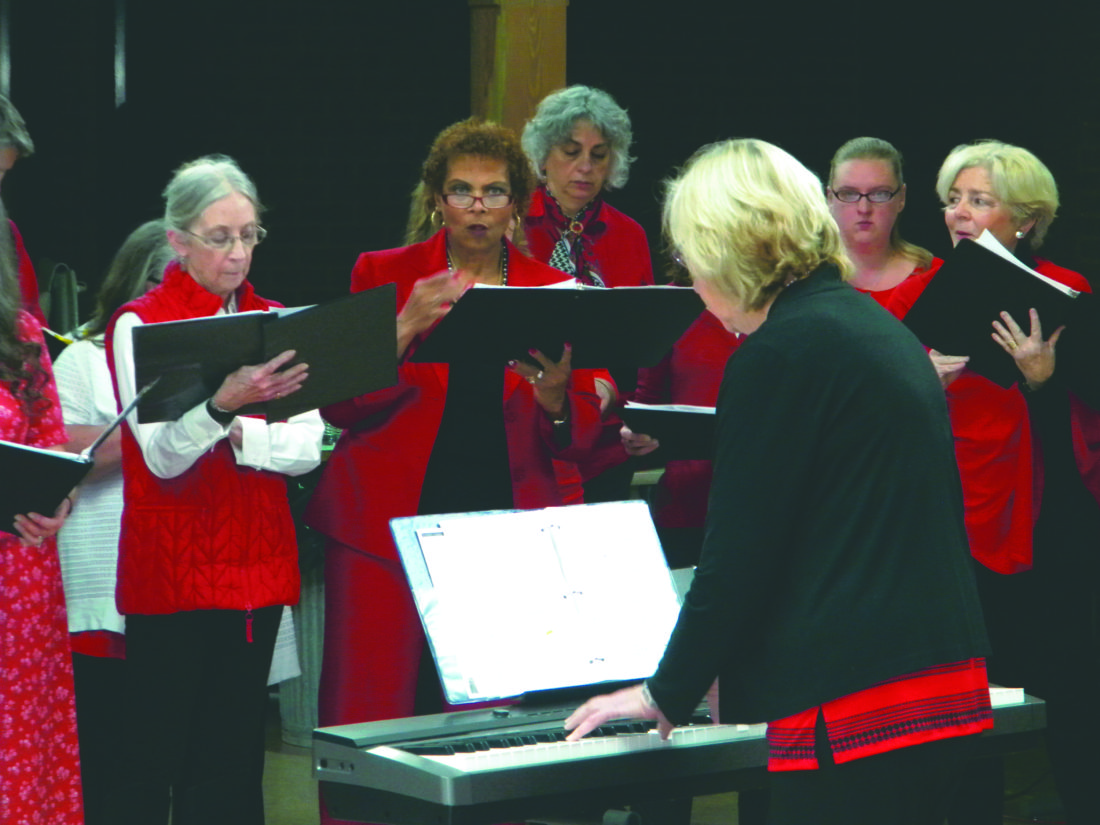 Journal photo by Jim McConville Elaine Rendler, director of music ministry at St. Agnes Catholic Church in Shepherdstown, leads the church choir in a Valentine's Day tribute concert for Army veterans at the Martinsburg Veterans Affairs Medical Center on Sunday.