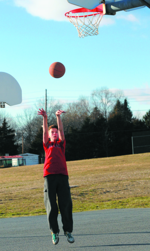 17 Chilly Hoops ra 02-16-17 Michael Maddox, 12 yrs old, takes advantage of teh sunny blue sky day to shoot hoops outside on the Opequon Elementary School playground Thursday afternoon. (Journal Photo by Ron Agnir)