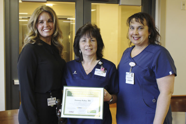 WVU Medicine Berkeley Medical Center's fourth quarter 2016 recipient of the DAISY Award For Extraordinary Nurses Donna Autry, center, is pictured receiving her award from Samantha Richards, left, vice president/chief nursing officer at WVU Medicine University Healthcare and Andrea Hartman, right, nurse director of the outpatient cancer and infusion center. (Submitted photo)
